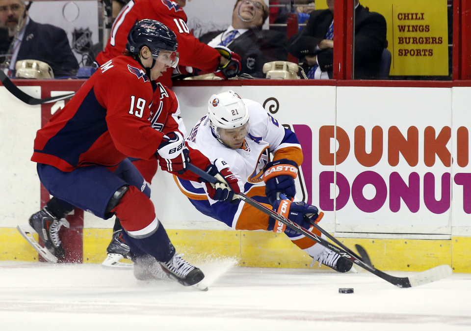 Photo - Washington Capitals center Nicklas Backstrom (19), from Sweden, and New York Islanders right wing Kyle Okposo (21) work to get the puck in the second period of an NHL hockey game, Tuesday, Feb. 4, 2014, in Washington. (AP Photo/Alex Brandon)