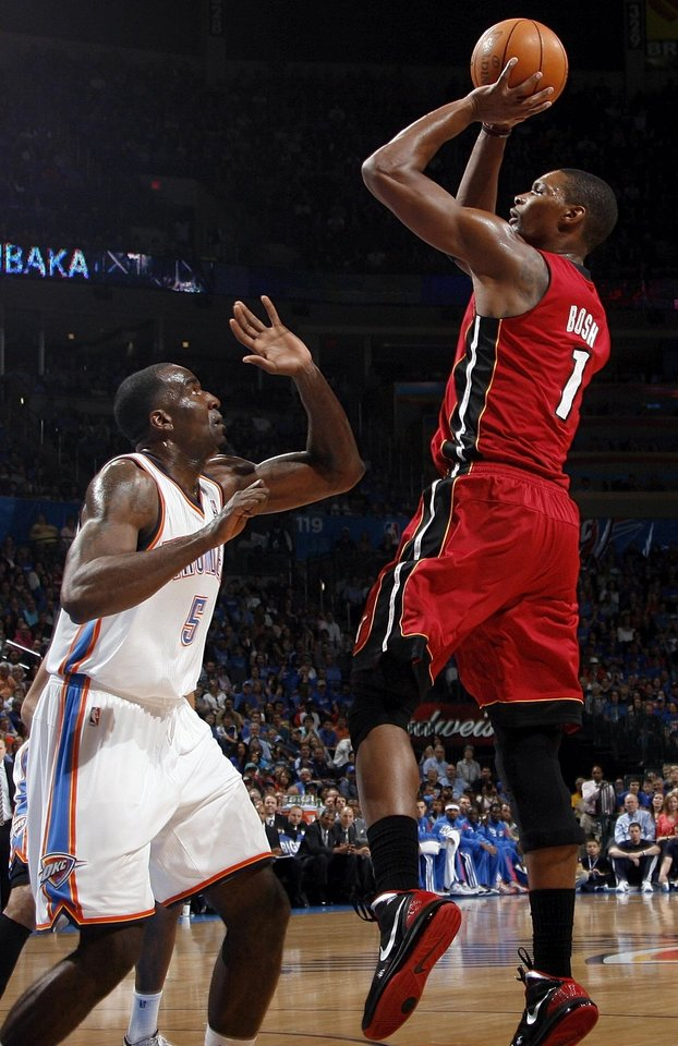 Photo - Miami's Chris Bosh (1) shoots over Oklahoma City's Kendrick Perkins (5) during the NBA basketball game between the Miami Heat and the Oklahoma City Thunder at Chesapeake Energy Arena in Oklahoma City, Sunday, March 25, 2012. Photo by Nate Billings, The Oklahoman