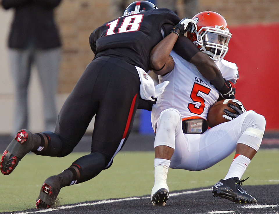 Texas Tech's Micah Awe (18) stops Oklahoma State 's Josh Stewart (5) during the college football game between the Oklahoma State University Cowboys (OSU) and the Texas Tech University Red Raiders (TTU) at Jones AT&T Stadium in Lubbock, Tex. on Saturday, Nov. 2, 2013.  Photo by Chris Landsberger, The Oklahoman