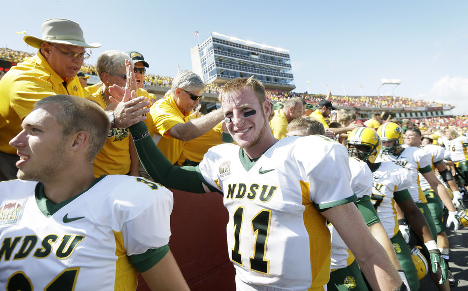 Photo - North Dakota State quarterback Carson Wentz (11) celebrates with fans after their 34-14 win over Iowa Stae in an NCAA college football game, Saturday, Aug. 30, 2014, in Ames, Iowa. (AP Photo/Charlie Neibergall)
