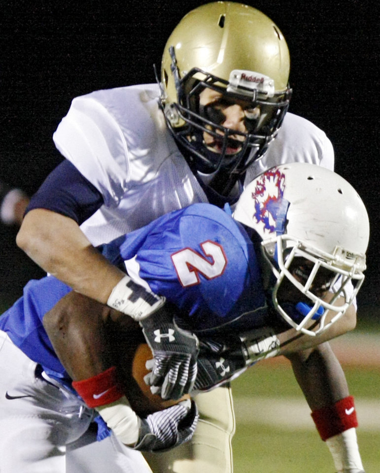 Kingfisher's Jordan Woods (18) brings down Millwood's Emilio Gatewood (2) during the Class 2A State semifinal football game between Millwood High School and Kingfisher High School on Saturday, Dec. 5, 2009, in Yukon, Okla. 