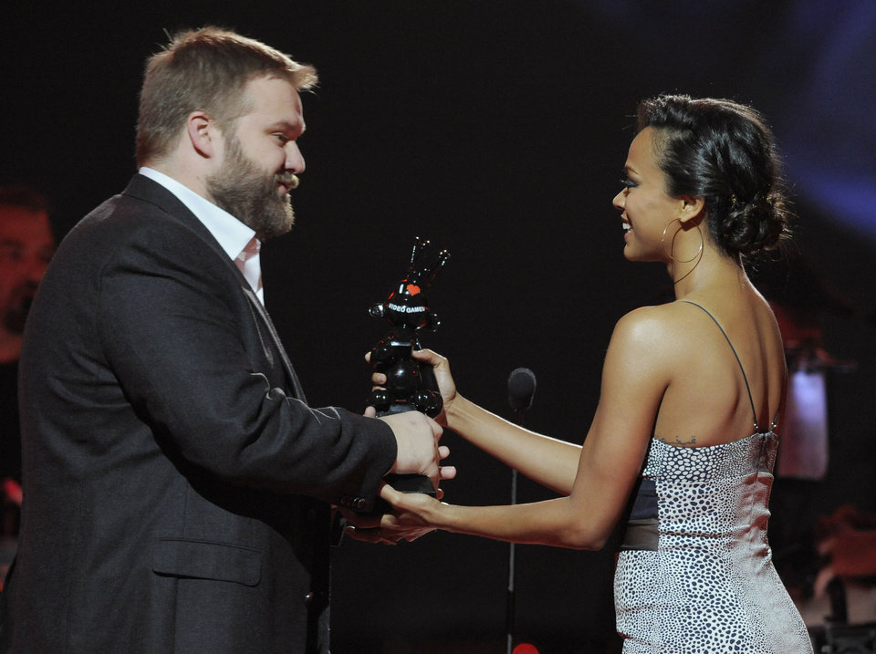 "Zoe Saldana, right, presents the award for game of the year to Robert Kirkman for ""Walking Dead: The Game"" on stage at Spike's 10th Annual Video Game Awards at Sony Studios on Friday, Dec. 7, 2012, in Culver City, Calif. (Photo by Chris Pizzello/Invision/AP)"