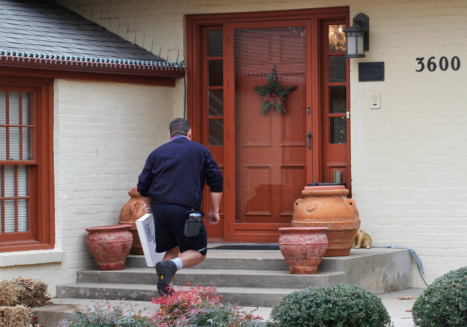 Longtime FedEx driver Ray Beltrane runs up to the front door of this home in northwest Oklahoma City to deliver a package on Monday, Dec. 12, 2011. Photo by Jim Beckel, The Oklahoman