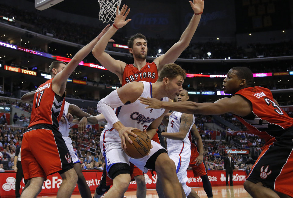 Los Angeles Clippers\' Blake Griffin, center, is defended by Toronto Raptors\' Jonas Valanciunas, left, of Lithuania, Kyle Lowry, right, and Andrea Bargnani, of Italy, in the first half of an NBA basketball game in Los Angeles, Sunday, Dec. 9, 2012. (AP Photo/Jae C. Hong)