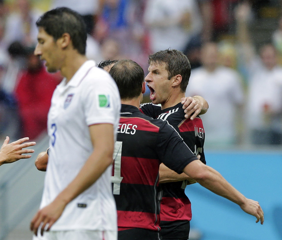 Photo - Germany's Thomas Mueller, right, celebrates scoring the opening goal as United States' Omar Gonzalez, left, walks away during the group G World Cup soccer match between the USA and Germany at the Arena Pernambuco in Recife, Brazil, Thursday, June 26, 2014. (AP Photo/Matthias Schrader)