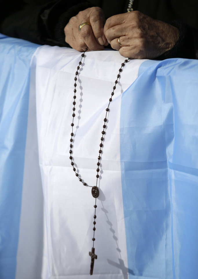 "A faithful holds a rosary over an Argentine flag in St. Peter's square at the Vatican on the occasion of the celebration of the Easter Mass Sunday, March 31, 2013. ""Our daily problems and worries can wrap us up in ourselves, in sadness and bitterness, and that is where death is,"" he said. ""Let the risen Jesus enter your life, welcome him as a friend, with trust: he is life!"" said Pope Francis during the Easter vigil. (AP Photo/Andrew Medichini)"