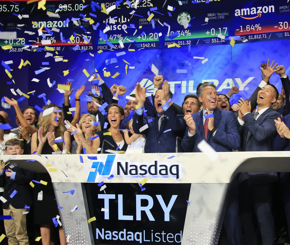 Photo -  Brendan Kennedy, third from right in front, CEO and founder of British Columbia-based Tilray Inc., a major Canadian marijuana grower, leads cheers as confetti falls to celebrate his company's IPO (TLRY) on July 19 at Nasdaq in New York. Investors are craving marijuana stocks as Canada prepares to legalize pot next month, leading to giant gains for Canada-based companies listed on U.S. exchanges. [AP FILE PHOTO]