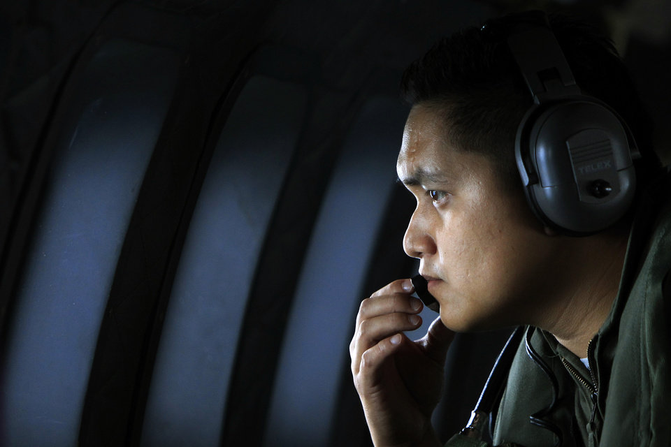 Photo - A crew member of a Royal Malaysian Air Force CN-235 aircraft looks out the window during a search and rescue operation for the missing Malaysia Airlines plane over the Straits of Malacca, Thursday, March 13, 2014. Planes sent Thursday to check the spot where Chinese satellite images showed possible debris from the missing Malaysian jetliner found nothing, Malaysia's civil aviation chief said, deflating the latest lead in the six-day hunt. The hunt for the missing Malaysia Airlines flight 370 has been punctuated by false leads since it disappeared with 239 people aboard about an hour after leaving Kuala Lumpur for Beijing early Saturday. (AP Photo/Lai Seng Sin)