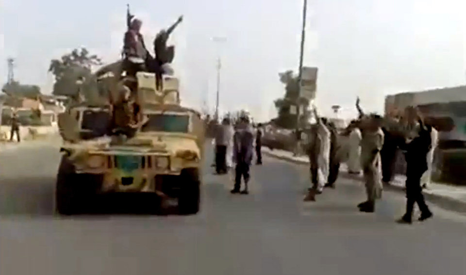 Photo - In this Tuesday, June 17, 2014 image taken from video uploaded to a militant social media account, which has been authenticated based on its contents and other AP reporting, al-Qaida-inspired Islamic State of Iraq and the Levant militants raise their weapons as they arrive to the country's largest oil refinery in Beiji, some 250 kilometers (155 miles) north of the capital, Baghdad, Iraq. Iraqi security forces battled insurgents targeting the country's main oil refinery and said they regained partial control of a city near the Syrian border Wednesday, trying to blunt a weeklong offensive by Sunni militants who diplomats fear may have also seized some 100 foreign workers. (AP Photo via militant video)