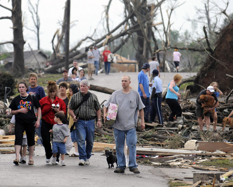 Photo - People walk down Magnolia Lane after a tornado touched down in Concord, Ala., outside of Hueytown late Wednesday, April 27, 2011. The damage in the area is extensive with homes and businesses destroyed and people injured. (AP Photo/Birmingham News, Jeff Roberts)
