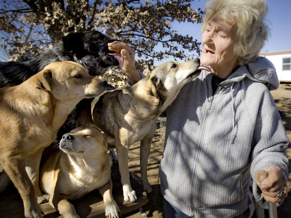 Photo - Catherine Titus get just a little bit of attention as she sits with a mere few of the 100 plus dogs she care for on Tuesday, Dec. 30, 2008, in Wilson, Okla. Titus who live out of a broken down van with no running water or electricity spends most all of her monthly $700 Social Security check to care for the dogs she calls her best friends.  Titus makes sure the dogs are fed twice a day, and are also given dog treats as a little something extra.