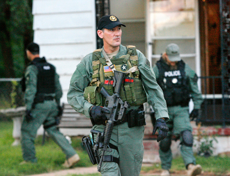 Officers outside a Mustang home after making entry at dawn as part of a  multi-agency drug raid that targeted meth operations throughout the state Tuesday, June 29, 2010.  Oklahoma Bureau of Narcotics officers teamed with ICE agents  and local law enforcement to execute 13 search warrants and 18 arrest warrants. Photo  by Jim Beckel, The Oklahoman ORG XMIT: KOD