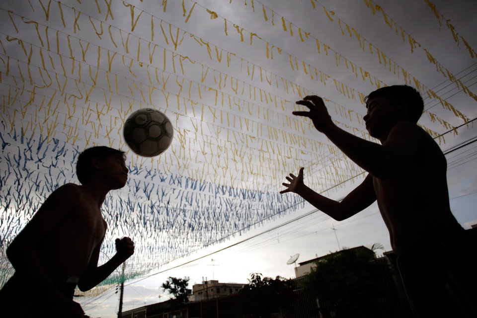 Photo - Boys play ball in a street decorated for the upcoming World Cup in Brasilia, Brazil, Friday, May 23, 2014. Brasilia is one of the host cities for the upcoming international soccer tournament that starts in June. (AP Photo/Eraldo Peres)