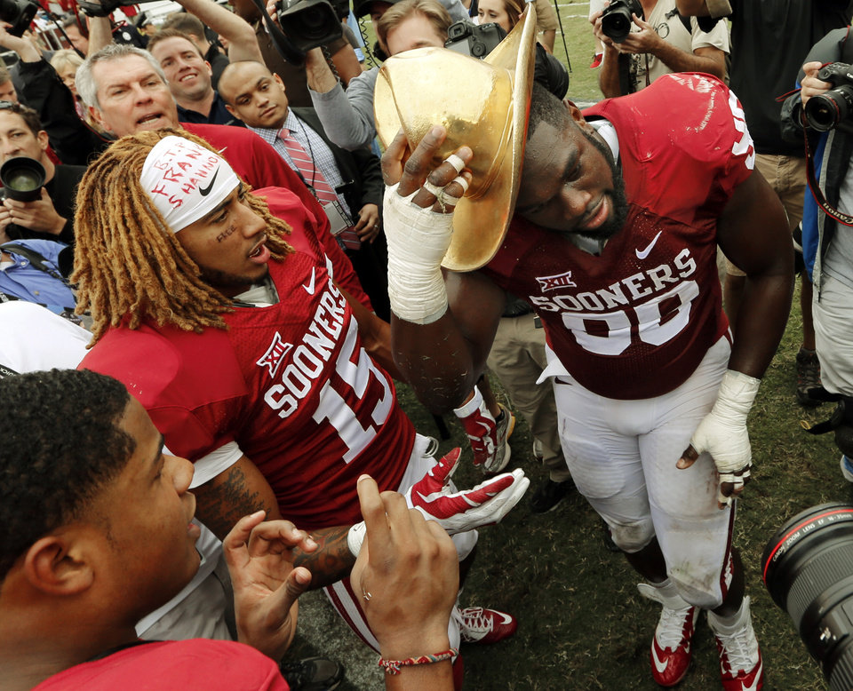 Photo - Oklahoma's Zack Sanchez (15) and Chuka Ndulue don the Golden Hat trophy after the Red River Showdown college football game where the University of Oklahoma Sooners (OU) defeated the University of Texas Longhorns (UT)  31-26 at the Cotton Bowl in Dallas, Texas on Saturday, Oct. 11, 2014. 
