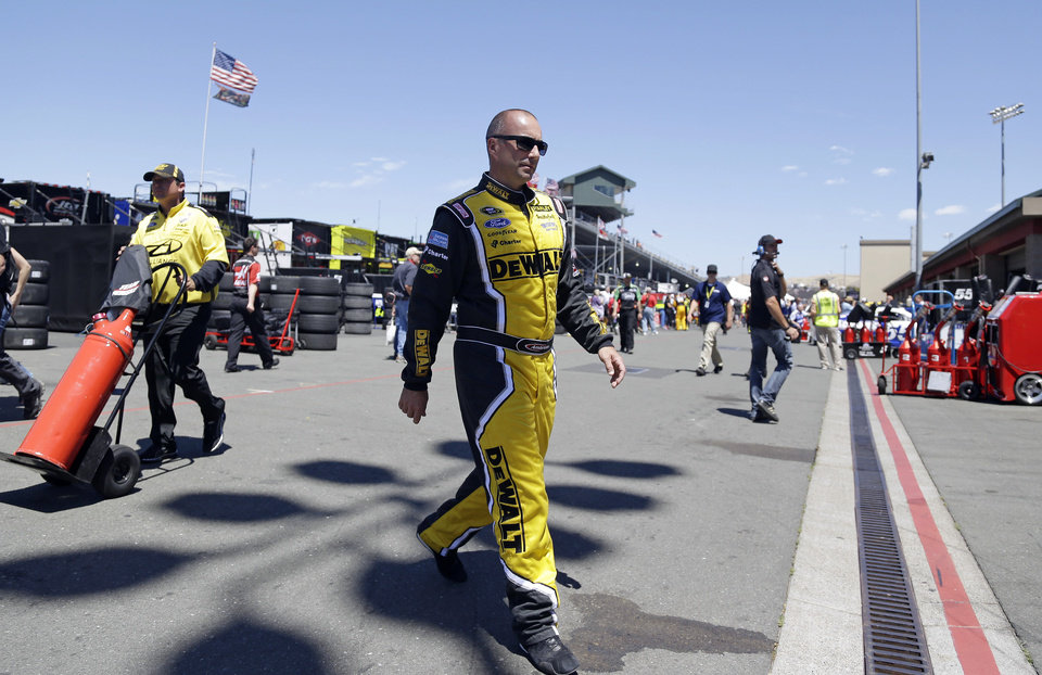 Photo - Marcos Ambrose walks to his car before the start of practice for the NASCAR Sprint Cup Series auto race Friday, June 20, 2014, in Sonoma, Calif. Ambrose wants nothing more than to break Hendrick Motorsports' four-race winning streak. His best shot comes Sunday on the road course at Sonoma Raceway, where a win could earn the Australian his first berth in the Chase for the Sprint Cup championship. (AP Photo/Eric Risberg)
