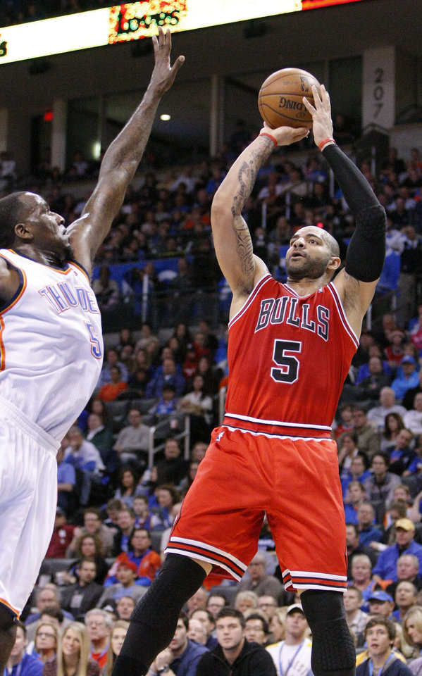 Photo - Chicago Bulls forward Carlos Boozer goes up for a basket as Oklahoma City Thunder center Kendrick Perkins defends during the first quarter of an NBA basketball game in Oklahoma City, Sunday, Feb. 24, 2013. (AP Photo/Alonzo Adams)