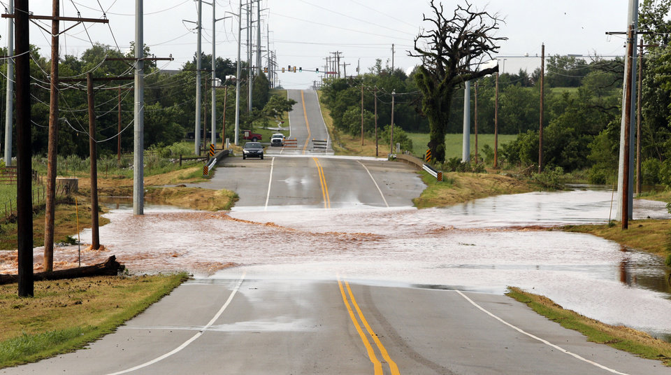 Photo - Water was still over the roadway south of Moore Norman Technology Center at 8:00 am. on Saturday, June 1, 2013 in Norman, Okla.  Many roads in the area were closed because of flood water during Friday night's storm.  Photo by Steve Sisney, The Oklahoman