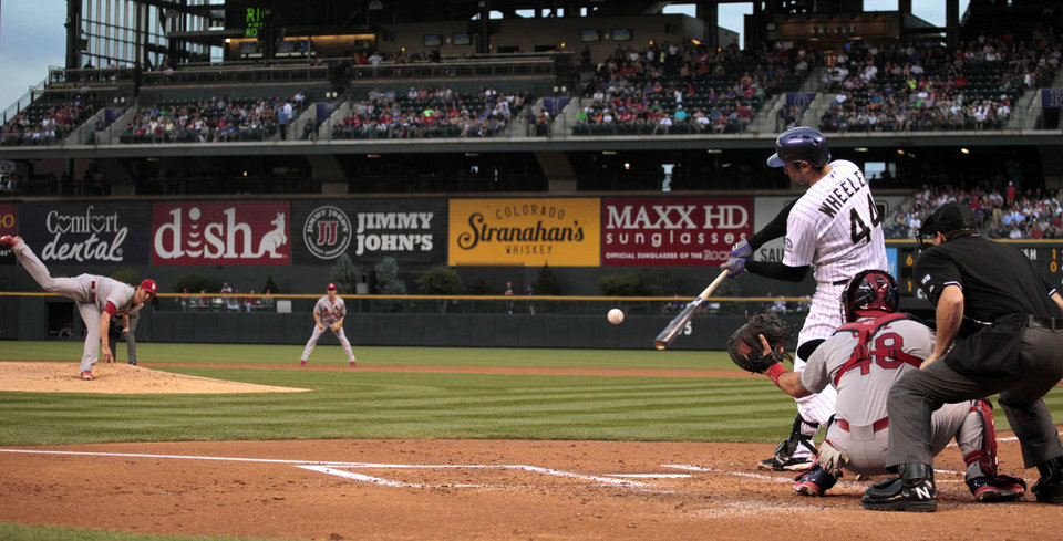 Photo - Colorado Rockies' Ryan Wheeler hits a two-run single against St. Louis Cardinals starting pitcher Shelby Miller in the first inning of a baseball game in Denver on Tuesday, June 24, 2014. Cardinals catcher Tony Cruz waits for the pitch. (AP Photo/Joe Mahoney)