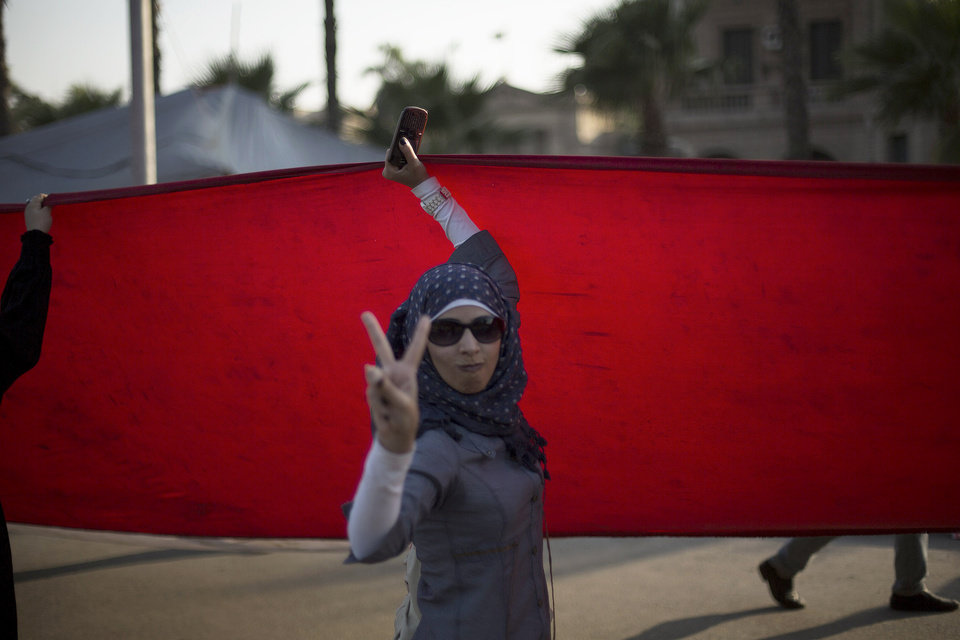 Supporter of ousted Egypt's Islamist President Mohammed Morsi makes the victory during a rally near the University of Cairo, in Cairo, Egypt, Thursday, July 4, 2013. The chief justice of Egypt's Supreme Constitutional Court was sworn in Thursday as the nation's interim president, taking over hours after the military ousted the Islamist President Mohammed Morsi. Adly Mansour took the oath of office at the Nile-side Constitutional Court in a ceremony broadcast live on state television. According to military decree, Mansour will serve as Egypt's interim leader until a new president is elected. A date for that vote has yet to be set. (AP Photo/ Manu Brabo)