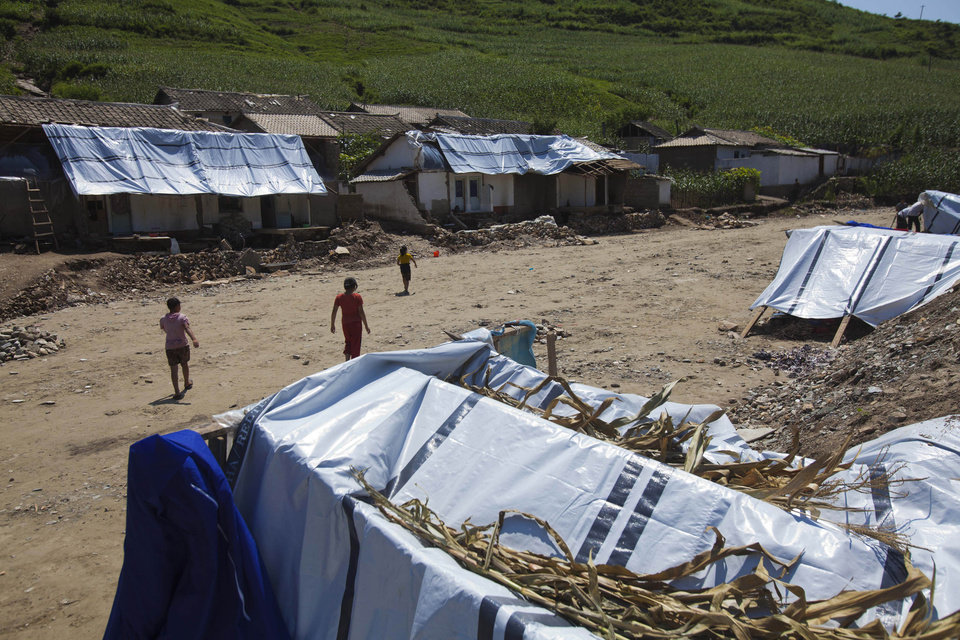 In this Monday, Aug 13, 2012 photo, displaced North Korean women, left homeless by July flooding, walk among temporary tents set up in their destroyed neighborhood in Ungok, North Korea. Twin typhoons are renewing fears of a humanitarian crisis in North Korea, where poor drainage, widespread deforestation and fragile infrastructure can turn even a routine rainstorm into a catastrophic flood. (AP Photo/David Guttenfelder)