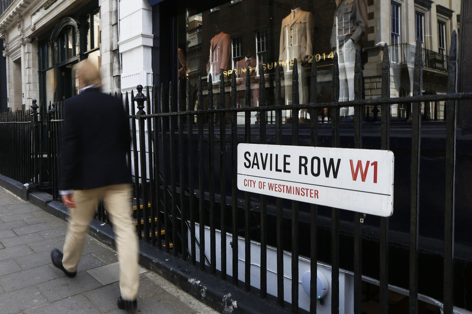 Photo - In this photo taken Friday, June 6, 2014, a man walks down Savile Row in London. In the world of women's fashion, London often seems to play second fiddle to other style capitals: It lacks the allure of Paris's haute couture, or the polish of Milan's luxury labels. But it's a whole different story when it comes to dressing men. Steeped in a rich history of tailoring for kings, army generals and the world's wealthiest men, London is now marketed as the home of men's fashion - the original birthplace of the tuxedo jacket, the bowler hat and the three-piece suit, among other classic items. When trendy designers like Alexander McQueen and Burberry kick off the new season's menswear shows in the British capital Sunday, the catwalks will be staged just blocks away from elite tailoring houses that have been perfecting their craft for over a century. Savile Row, a street lined with more than a dozen tailors and a living museum of the English love affair with luxury menswear, has a long-standing tradition closely tied to a history in royal dress, military uniforms and gentry sports like horseback riding and hunting. (AP Photo/Sang Tan)