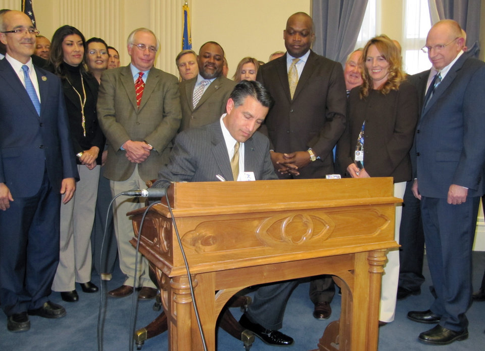 Photo - Gov. Brian Sandoval, surrounded by state lawmakers in the state's Old Assembly Chambers, signs AB114 legalizing online gambling in Nevada on Thursday, Feb. 21, 2013 in Carson City. (AP Photo/Sandra Chereb).