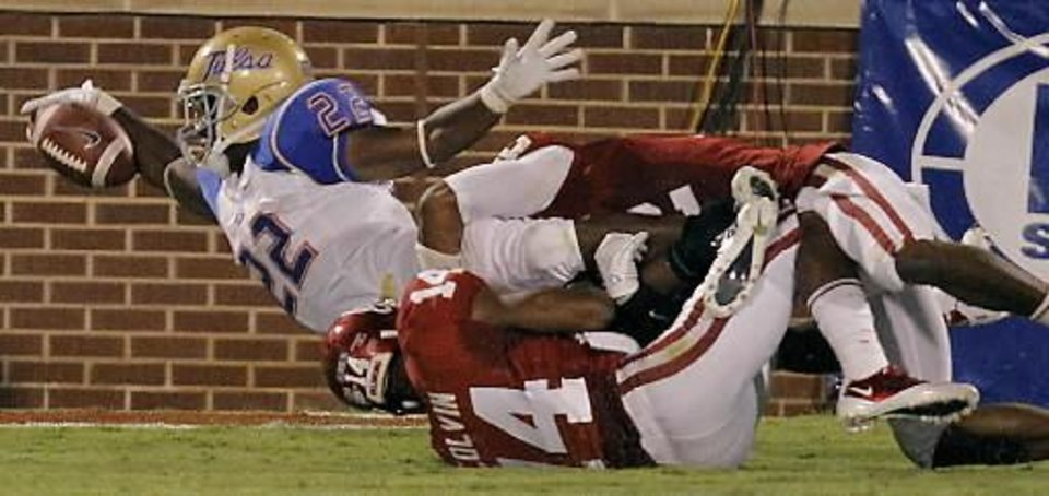 Photo - Tulsa's Trey Watts (22) dives for a touchdown over Oklahoma's Aaron Colvin (14) during the college football game between the University of Oklahoma Sooners ( OU) and the Tulsa University Hurricanes (TU) at the Gaylord Family-Memorial Stadium on Saturday, Sept. 3, 2011, in Norman, Okla. Photo by Chris Landsberger, The Oklahoman ORG XMIT: KOD