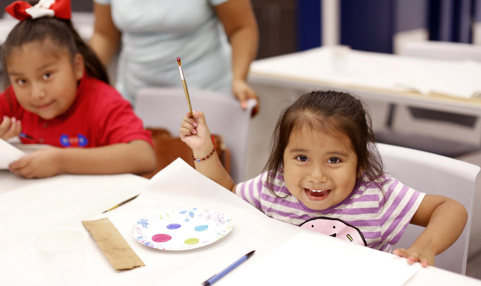 Photo -  Alexa Martinez, 3, right, and Allison Salas, a second grade student at Dove Academy, work on projects at Capitol Hill Library. [Photo by Jim Beckel, The Oklahoman]