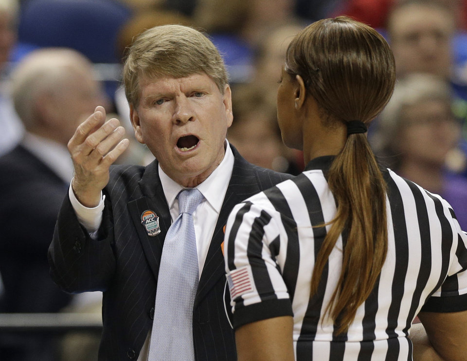 Photo - North Carolina head coach Andrew Calder, left, argues a call during the first half of an NCAA college basketball semi-final game against Duke at the Atlantic Coast Conference tournament in Greensboro, N.C., Saturday, March 8, 2014. (AP Photo/Chuck Burton)