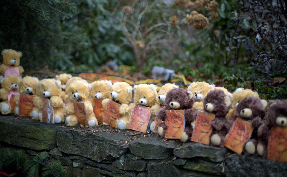 Photo - Teddy bears, each representing a victim of the Sandy Hook Elementary School shooting, sit on a wall at a sidewalk memorial, Sunday, Dec. 16, 2012, in Newtown, Conn. A gunman walked into Sandy Hook Elementary School in Newtown Friday and opened fire, killing 26 people, including 20 children. (AP Photo/David Goldman)