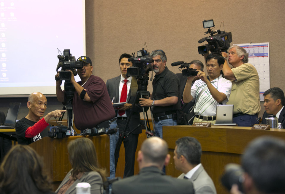 Photo - Sriracha hot sauce founder David Tran, at podium, left, addresses a city council meeting in Irwindale, Calif., Wednesday, April 23, 2014. The city of Irwindale is suing the maker of Sriracha hot sauce and last week the Los Angeles suburb tentatively voted to declare the bottling plant a public nuisance. Irwindale City Attorney Fred Galante says relocating seems extreme and the city only wants to see the smell issue addressed. (AP Photo/Damian Dovarganes)