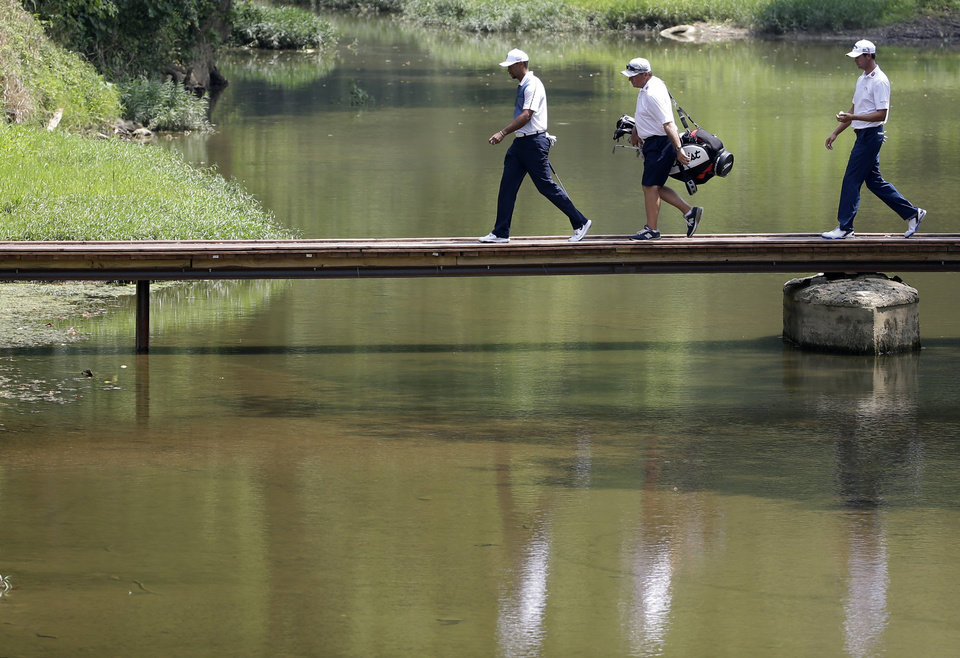 Photo - Tiger Woods, left, and Steve Stricker, right cross the foot bridge on the second hole during a practice round for the PGA Championship golf tournament at Valhalla Golf Club on Wednesday, Aug. 6, 2014, in Louisville, Ky. The tournament is set to begin on Thursday. (AP Photo/David J. Phillip)