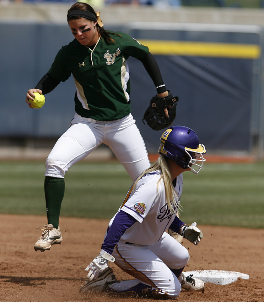 USF's Alexis Nowell (22) jumps over LSU's Ashley Applegate (10) during a Women's College World Series game between Louisiana State University and the University of South Florida at ASA Hall of Fame Stadium in Oklahoma City, Saturday, June 2, 2012.  Photo by Garett Fisbeck, The Oklahoman