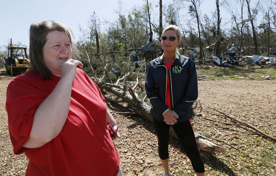 Photo - Standing amid debris, chicken farmer  Cindy Wilkes recalls for her friend Tosha McLemore, how she and her family rode out Monday's tornado that destroyed their Noxapater, Miss., home and flattened their neighboring 8-chicken house farm operation Wednesday, April 30, 2014. The farm raises broilers for Tyson and each house has 28,500 chickens. Several poultry raising farms near Louisville, were either destroyed or damaged by the storms. (AP Photo/Rogelio V. Solis)