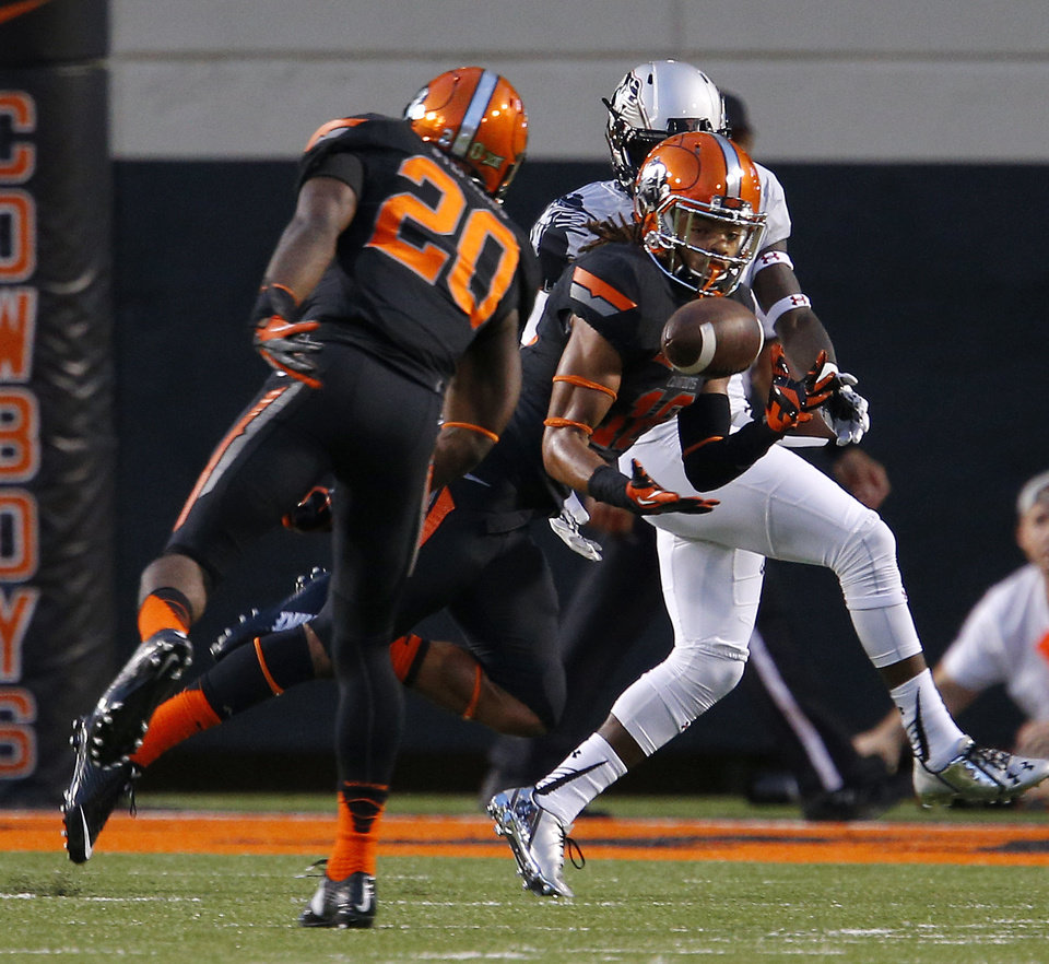 Photo - Oklahoma State's Ramon Richards (18) intercepts the ball during a college football game between the Oklahoma State Cowboys (OSU) and the Texas Tech Red Raiders at Boone Pickens Stadium in Stillwater, Okla., Thursday, Sept. 25, 2014. Photo by Bryan Terry, The Oklahoman