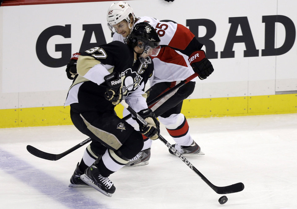 Photo - Pittsburgh Penguins' Sidney Crosby (87) gets past Ottawa Senators' Erik Karlsson (65) en route to a goal in the first period of Game 2 of an NHL hockey Stanley Cup second-round playoff series, in Pittsburgh on Friday, May 17, 2013. (AP Photo/Gene J. Puskar)