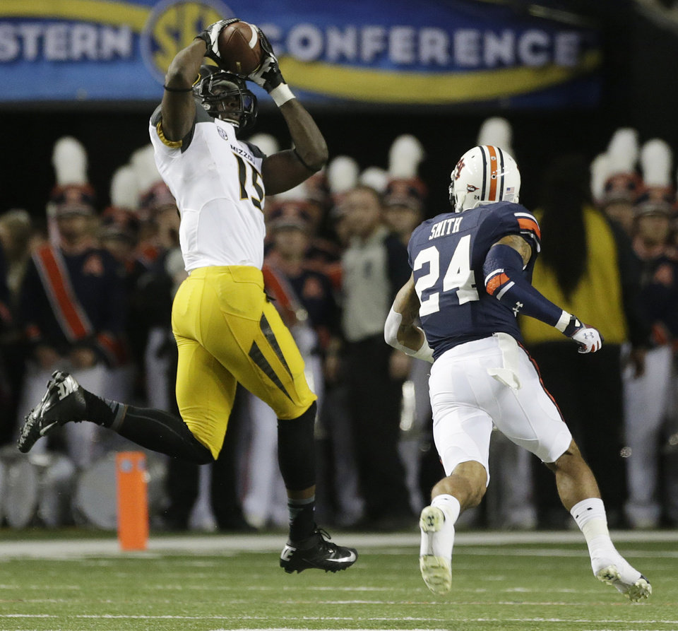 Missouri wide receiver Dorial Green-Beckham (15) makes the catch against Auburn defensive back Ryan Smith (24) during the first half of the Southeastern Conference NCAA football championship game, Saturday, Dec. 7, 2013, in Atlanta. Green-Beckham  scored on the play. (AP Photo/Dave Martin)