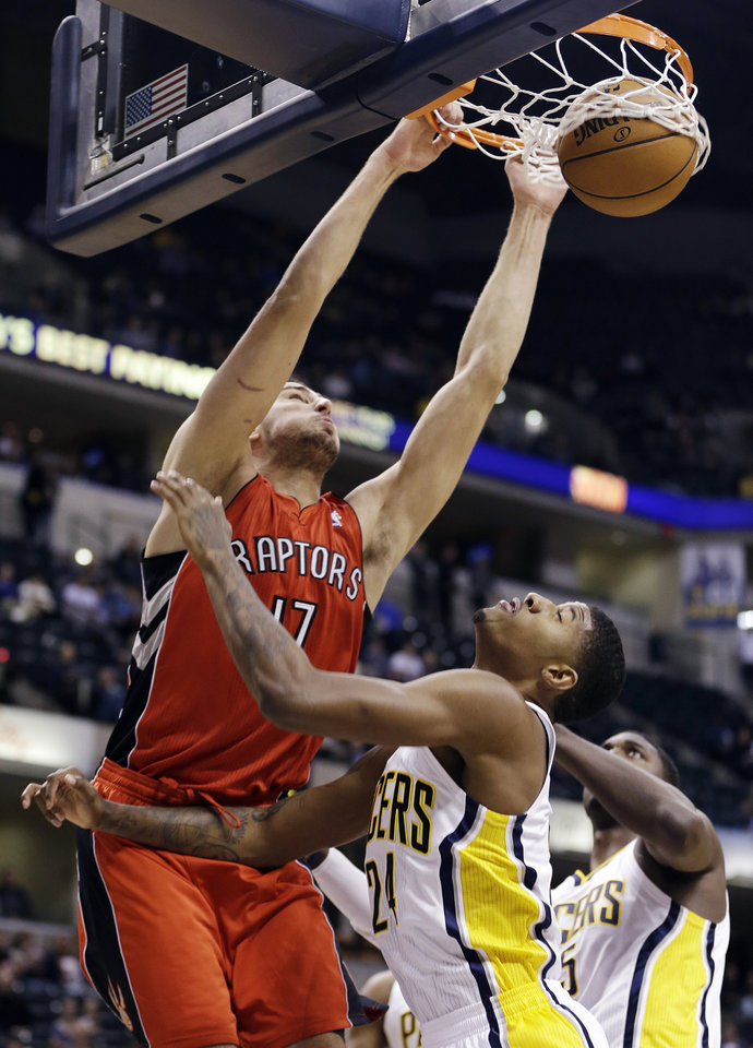 Toronto Raptors' Jonas Valanciunas (17) dunks against Indiana Pacers' Paul George (24) during the first half of an NBA basketball game, Tuesday, Nov. 13, 2012, in Indianapolis. (AP Photo/Darron Cummings)