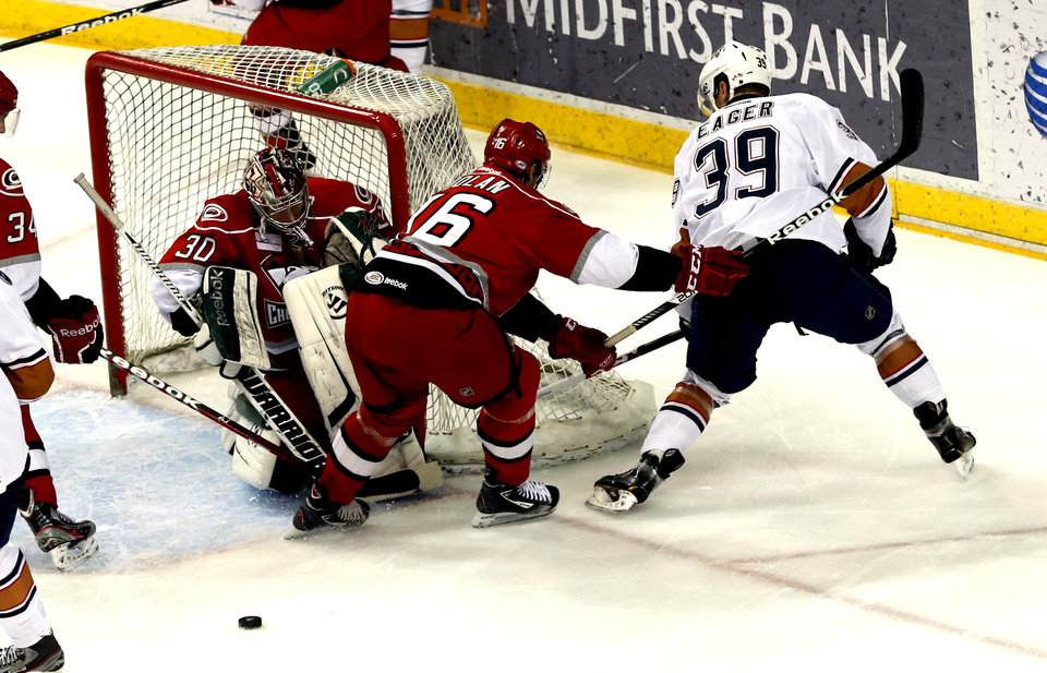 Charlotte's Sean Dolan tries to clear Ben Eager near the goal as goalie Rob Madores falls into the net in the first period during Game 2 of the AHL hockey playoff series between the Oklahoma City Barons and the Charlotte Checkers at the Cox Center in Oklahoma City, on Saturday, April 27, 2013.  Photo by Steve Sisney, The Oklahoman