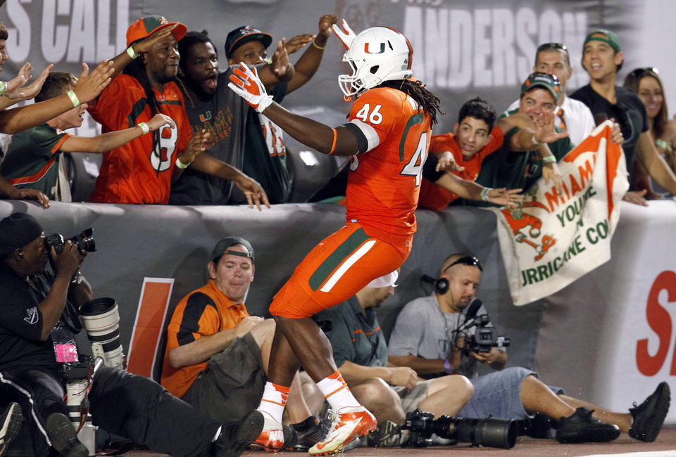 Photo -   Miami tight end Clive Walford (46) celebrates with fans after scoring a touchdown during the second half of an NCCA college football game against South Florida, Saturday, Nov. 17, 2012 in Miami. Miami defeated South Florida 40-9. (AP Photo/Wilfredo Lee)