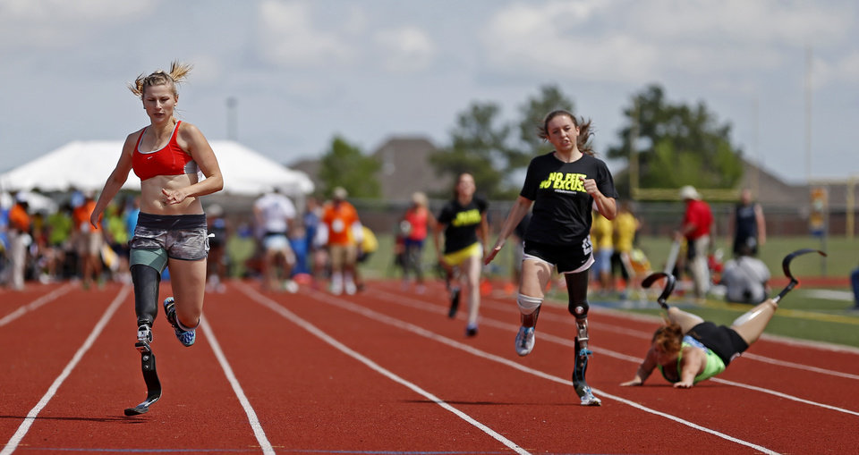 Tatsiana Khvitsko, left, races as a runner falls during the UCO Endeavor Games at the Edmond North High School School track, Saturday, June 7, 2014. Photo by Bryan Terry, The Oklahoman