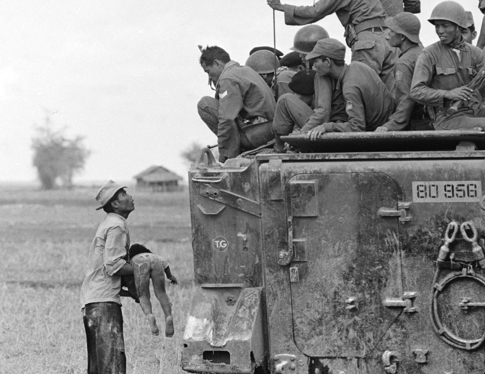 Photo -   FILE - In this March 19, 1964 file photo, one of several shot by Associated Press photographer Horst Faas which earned him the first of two Pulitzer Prizes, a father holds the body of his child as South Vietnamese Army Rangers look down from their armored vehicle. The child was killed as government forces pursued guerrillas into a village near the Cambodian border. Faas, a prize-winning combat photographer who carved out new standards for covering war with a camera and became one of the world's legendary photojournalists in nearly half a century with The Associated Press, died Thursday May 10, 2012. He was 79. (AP Photo/Horst Faas)