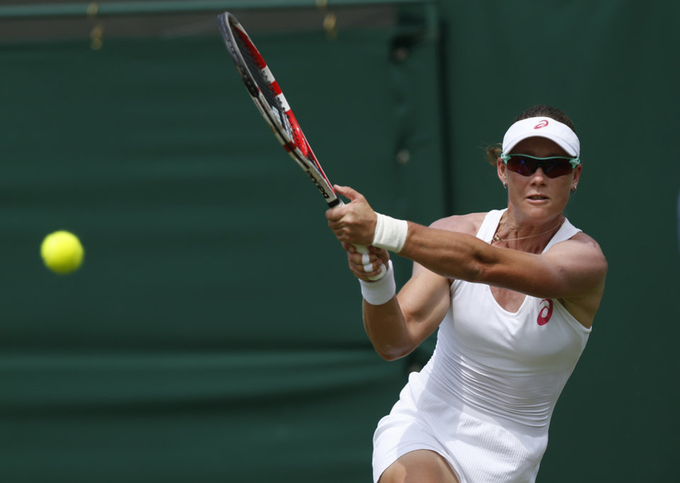 Photo - Australia's Samantha Stosur plays a return to Belgium's Yanina Wickmayer during their first round match at the All England Lawn Tennis Championships in Wimbledon, London,  Monday, June  23, 2014. (AP Photo/Sang Tan)