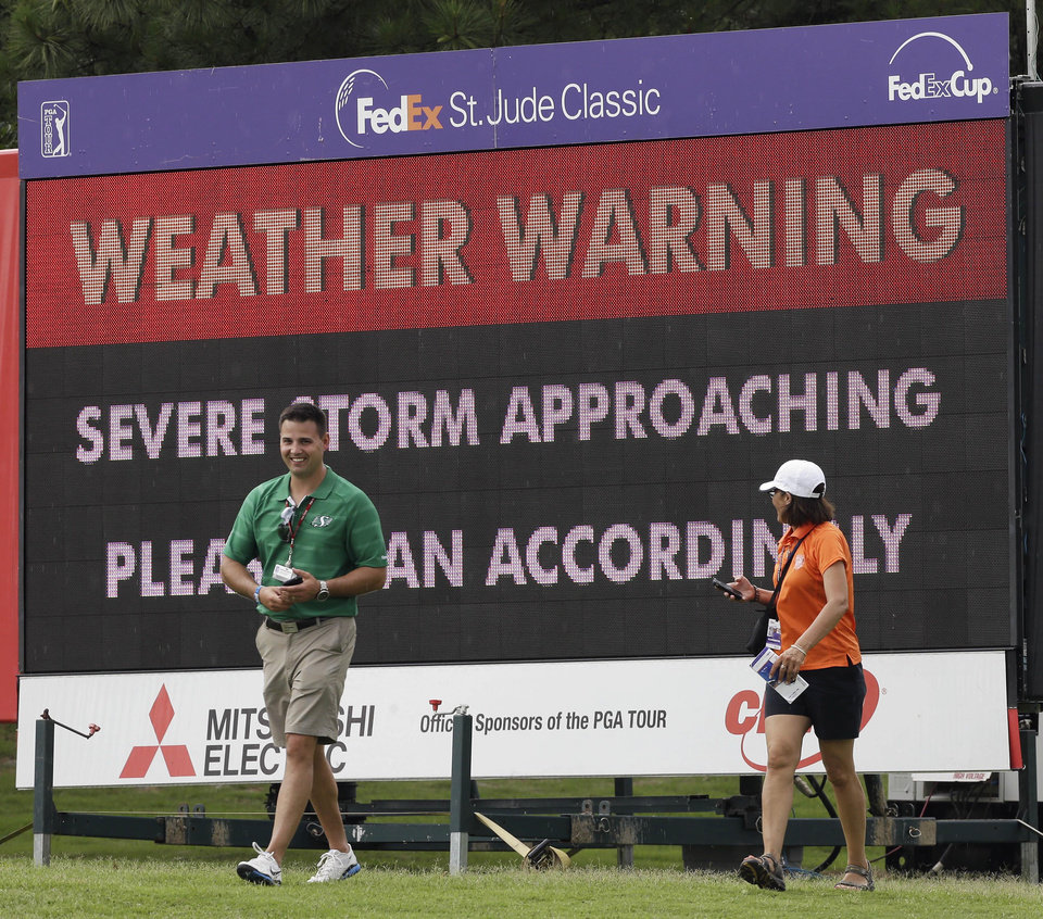 Photo - Fans head for shelter as an approaching storm stops play during the first round of the St. Jude Classic golf tournament Thursday, June 5, 2014, in Memphis, Tenn. (AP Photo/Mark Humphrey)