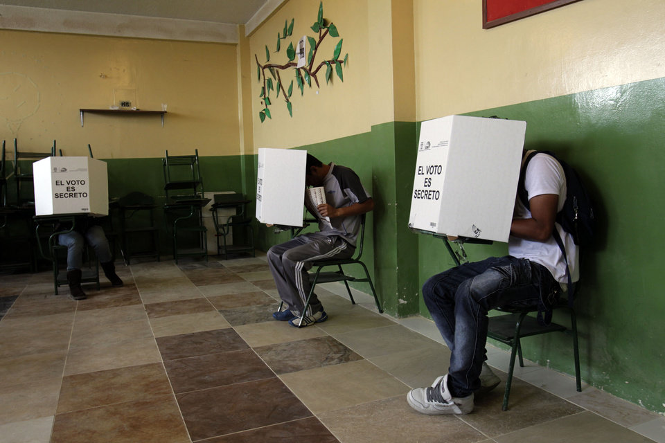 Voters fill their balots up at a polling station in Quito, Ecuador, Sunday, Feb.17, 2013. Ecuadoreans  elect president,  vice-president and National Assembly members Sunday with  President Rafael Correa highly favored to win a second re-election.(AP Photo/Dolores Ochoa)