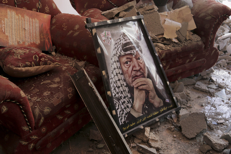 Photo - A poster of later Palestinian leader Yasser Arafat is seen on the rubble of a destroyed house in the Bureij refugee camp in the central Gaza Strip, Friday, Aug. 1, 2014. (AP Photo/Adel Hana)