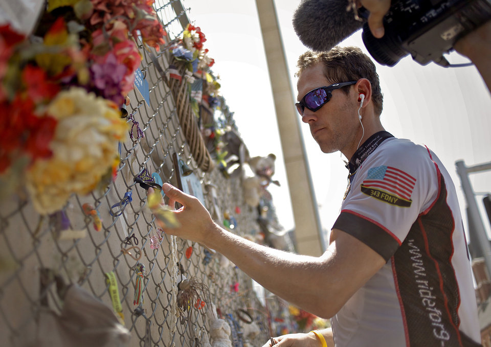 California firefighter Scott Smith hangs an item on the fence as he and other firefighters visit the Oklahoma City National Memorial during a stop while riding their bikes from California to New York to commemorate 9/11 anniversary on Friday, Aug. 12, 2011, in Oklahoma City, Okla. Photo by Chris Landsberger, The Oklahoman