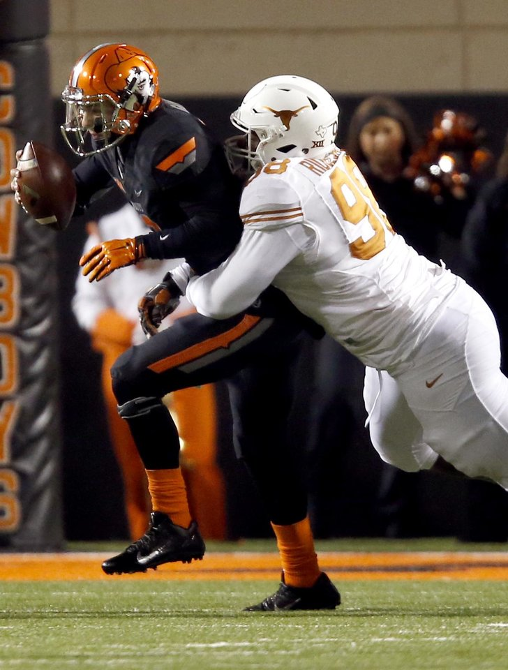 Photo - Oklahoma State's Daxx Garman (12) is sacked by Texas Hassan Ridgeway (98) during the college football game between the Oklahoma State University Cowboys (OSU) the University of Texas Longhorns (UT) at Boone Pickens Staduim in Stillwater, Okla. on Saturday, Nov. 15, 2014.  Photo by Sarah Phipps, The Oklahoman