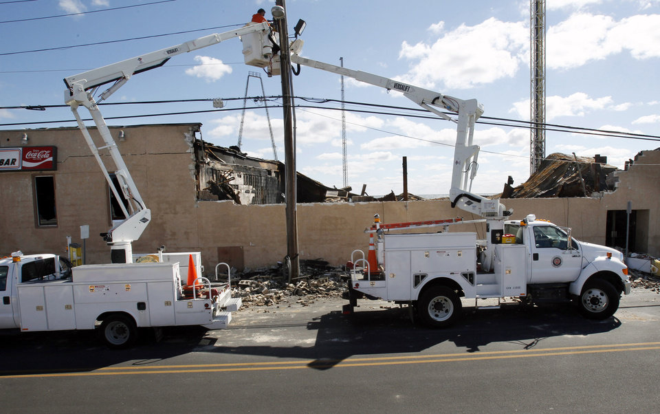 Photo - A crew works on power lines near the burned out buildings in Seaside Heights, N.J., Tuesday, Sept. 17, 2013, after a fire last Thursday that started near a frozen custard stand in Seaside Park,  quickly spread north into neighboring Seaside Heights. More than 50 businesses in the two towns were destroyed. The massive boardwalk fire in New Jersey began accidentally, the result of an electrical problem, an official briefed on the investigation said Tuesday. (AP Photo/Mel Evans)