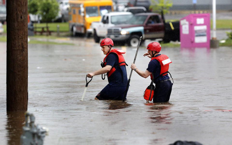 Photo - Two firefighters cross through deep water on SW 29 Street after heavy rains overwhelmed stormwater drainage systems and caused flooded streets, requiring  high water rescues in Oklahoma City as another round of severe storms passes through the metro.
